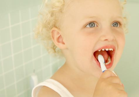 [Translate to Polski:] kid cleaning teeth